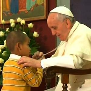World enchanted by boy who stayed at Pope's side