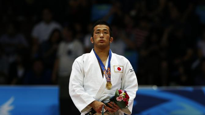 Japan's Hiroyuki Akimoto poses with his gold medal after defeating Mongolia's Odbayar Ganbaatar during their men's -73kg gold medal judo match at Dowon Gymnasium during the 17th Asian Games in Incheon