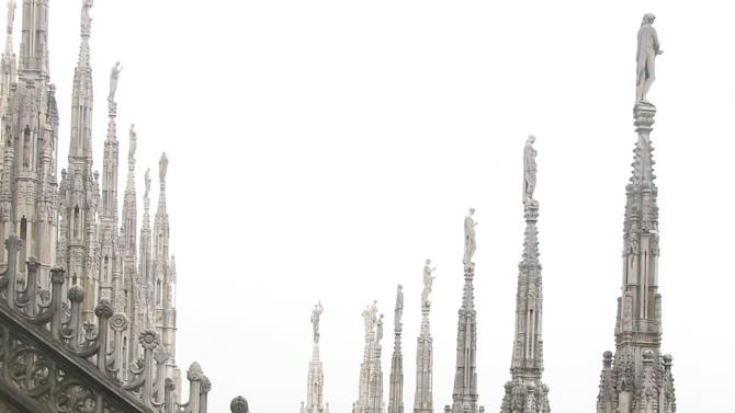 This July 6, 2012 photo shows a man looking at the spires of the Milan cathedral in Milan, Italy. To travel through northern Italy with a copy of Mark Twain's 1869 ''The Innocents Abroad', his classic 'record of a pleasure trip'. It took him to the great sights of Europe and on to Constantinople and Jerusalem before he sailed home to New York. Such a trip would take far too big a chunk out of my holiday time. But, Milan, Florence and Venice, a mere fragment for Twain, was within my reach for a two-week vacation. (AP Photo/Raf Casert)