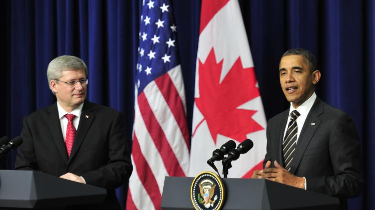 Canadian Prime Minister Stephen Harper, left, listens as U.S. President Barack Obama speaks following a meeting at the White House in Washington on Wednesday, Dec. 7, 2011. President Obama warned congressional Republicans that he would reject any effort to tie extraneous issues to an extension of the payroll tax cut, including the approval of an oil pipeline between the U.S. and Canada. (AP Photo/The Canadian Press, Paul Chiasson)
