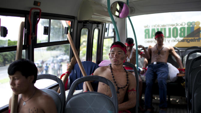 "Pemon Indigenous commute on a bus toward Germany's embassy in Caracas, Venezuela, Thursday, June 21, 2012.  Representatives of Venezuela's Pemon Indian tribe staged a protest outside Germany's embassy to demand the immediate repatriation of a rock they call the ""Kueka Stone,"" which is on public display in a Berlin park. A faction of Pemon Indians say the rock is an incarnation of their grandmother and they believe that the 1997 removal of the artifact by a German artist has resulted in natural disasters including a mudslide that killed thousands. (AP Photo/Ariana Cubillos)"