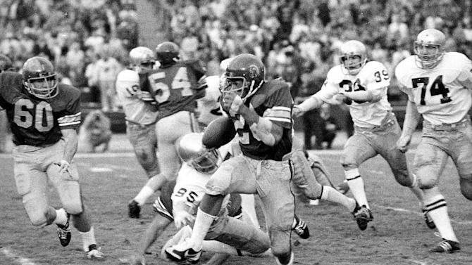 FILE - In this Nov. 30, 1974, file photo, Southern California's Anthony Davis breaks away from a tackle attempt by Notre Dame defensive end Ernie Hughes (95) as he runs 102 yards for a touchdown during the second half of their NCAA college football game in Los Angeles. Notre Dame's Tony Zappala (39) trails the play as Southern California's Clay Matthews follows. Davis ignited a 35-point third quarter and Southern California won 55-24, scoring all of its points in 17 minutes. The Associated Press takes a look at some of the memorable games in college football's greatest intersectional rivalry in anticipation of Southern California hosting No. 1 Notre Dame on Saturday, Nov. 24, 2012. (AP Photo/Jeff Robbins, File)