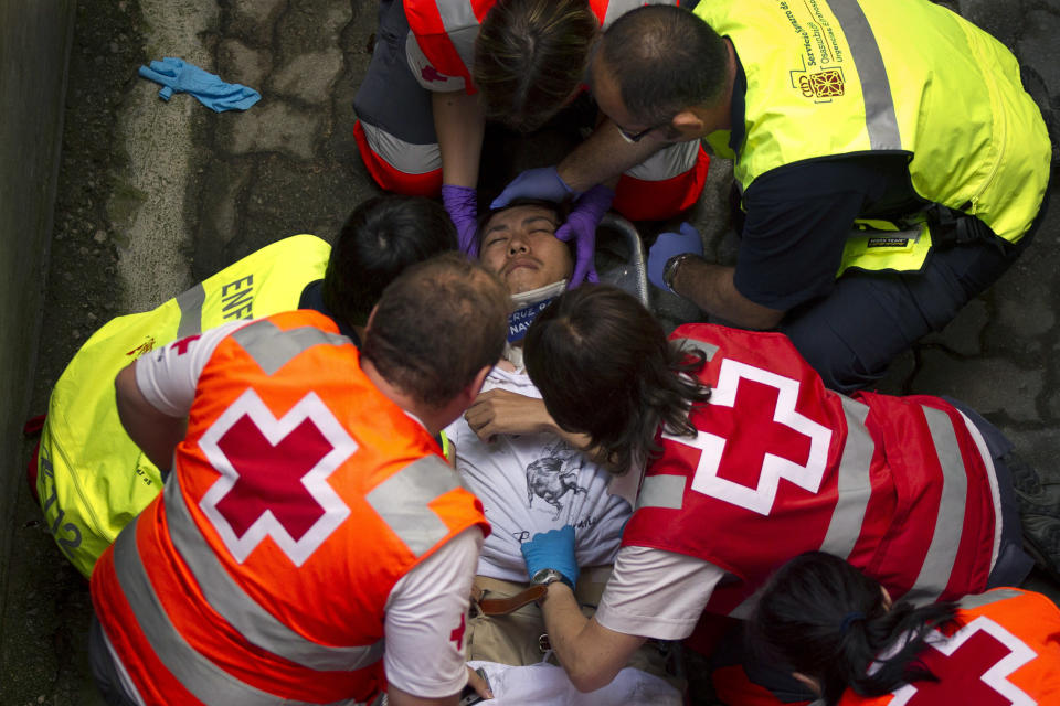 Doctors and paramedics give assistance to a reveler after a Dolores Aguirre Yabarra ranch fighting bull tossed him during the running of the bulls of the San Fermin festival, in Pamplona Spain, Saturday, July 7, 2012. (AP Photo/Daniel Ochoa de Olza)