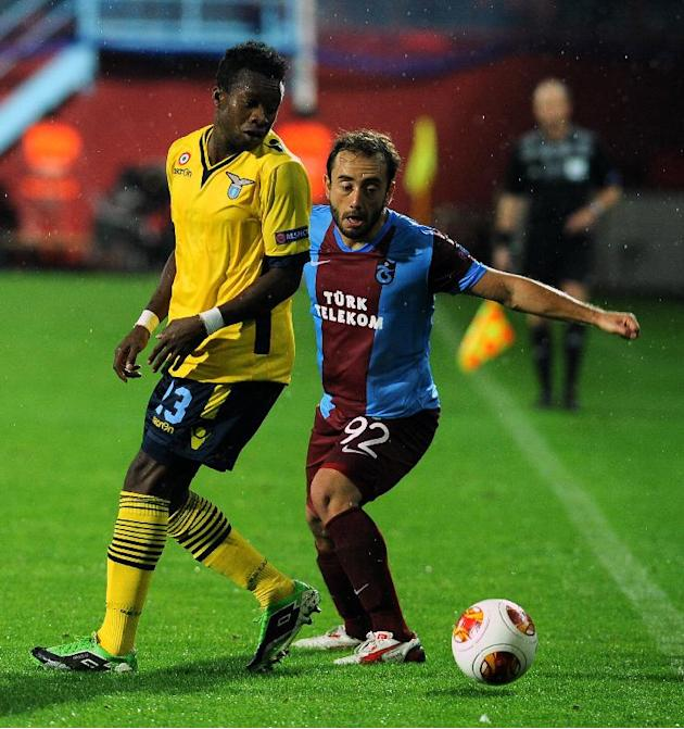 Orgenyi Onazi of Lazio, left, and Olcan Adin of Trabzonspor, fight for the ball during their Europa League soccer match in Trabzon, Turkey, Thursday, Oct. 3, 2013. (AP Photo)