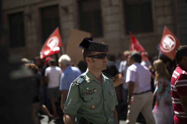 A Guardia Civil member stands guard as civil servants march condemning the recent austerity measures announced by the Spanish government, during a demonstrations in Madrid, Spain, on Friday July 13, 2