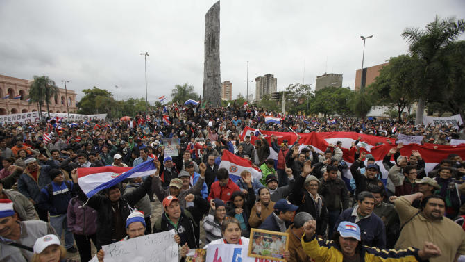 Supporters of Paraguay's President Fernando Lugo protest against Lugo's impeachment trial, outside Parliament, in Plaza de Armas, Asuncion, Paraguay, Friday, June 22, 2012. Paraguayan lawmakers voted Thursday to impeach Lugo for his role in for his role in a deadly clash involving landless farmers and police. Lugo's trial was to begin Friday in Paraguay's Senate. (AP Photo/Jorge Saenz)