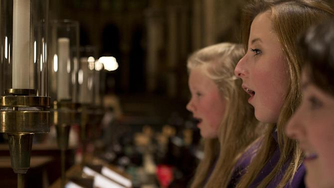 In this Wednesday, Jan. 22 2014 photo, choristers Poppy Braddy, centre, Chloe Chawner, right, and Abby Cox sing during an interview with the Associated Press in Canterbury Cathedral, Canterbury, England, as the first all female choir at the cathedral rehearses prior to their debut on Jan. 25. The pure, high voices of the choir soar toward the vaulted ceiling of Canterbury Cathedral as they have for more than 1,000 years. Just one thing is different - these young choristers in their purple cassocks are girls, and their public debut at Evensong on Saturday will end centuries of all-male tradition. Canterbury is not the first British cathedral to set up a girls' choir, but as mother church of the 80 million-strong Anglican Communion - one struggling with the role of women in its ranks - its move has special resonance. (AP Photo/Alastair Grant)