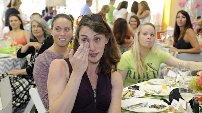 Expectant mom Ghandra Krueger of Greely, Colorado wipes a tear from her eye at Operation Shower, hosted by Melissa Joan Hart and sponsored by Carousel Designs at The 2012 Barclays, on Wednesday, Aug. 22, 2012 in Farmingdale, NY. Her husband, Robert Krueger is a Major in the Air Force. (Photo by Kathy Kmonicek/Invision for Carousel Designs/AP Images)
