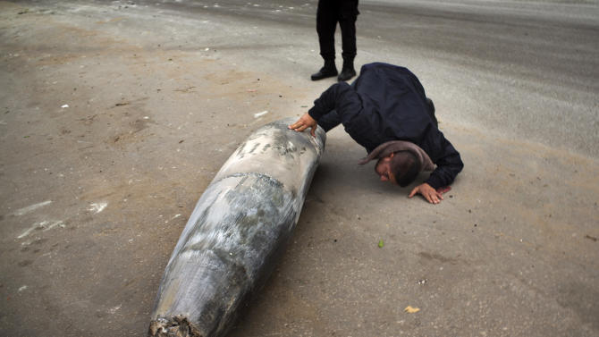A Hamas officer inspects an unexploded Israeli bomb in Gaza City, Saturday, Nov. 17, 2012. Israel bombarded the Hamas-ruled Gaza Strip with more than 180 airstrikes early Saturday, the military said, widening a blistering assault on militant operations to include the prime minister's headquarters, a police compound and a vast network of smuggling tunnels. The new attacks followed an unprecedented rocket strike aimed at the contested holy city of Jerusalem that raised the stakes in Israel's violent confrontation with Palestinian militants. (AP Photo/Bernat Armangue)