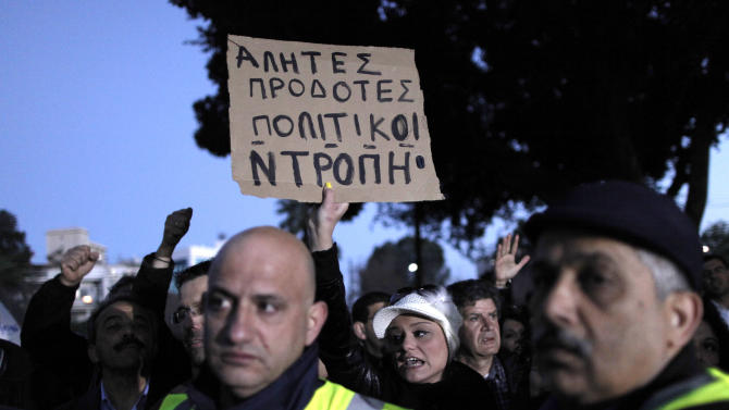 A bank employee holds a placard that reads in Greek: ''Bums, Traitors, Politicians, Same'' protest on Saturday, March 23, 2013. Thousands of bank employees took part in a protest that ended outside the Cypriot parliament. Politicians in Cyprus were racing Saturday to complete an alternative plan raising funds necessary for the country to qualify for an international bailout, with a potential bankruptcy just three days away. (AP Photo/Petros Giannakouris)