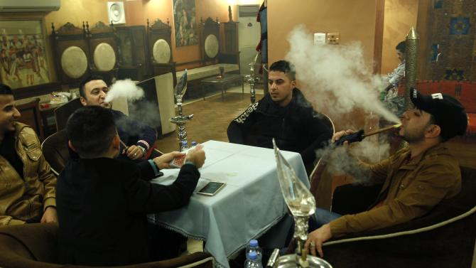 Men smoke shisha at a cafe in Baghdad