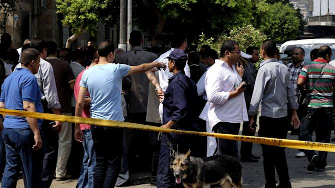 Egyptian security forces inspect the scene after a roadside bomb went off on a busy street in downtown near the foreign ministry, in Cairo, Egypt, Sunday, Sept. 21, 2014. Security officials said the Sunday explosion targeted a police checkpoint near the back gate of the ministry building. Several people were wounded, and senior policemen killed said the officials. (AP Photo/Aly Hazzaa, El Shorouk) EGYPT OUT