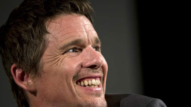 """US actor Ethan Hawke smiles during a press conference in Bucharest, Romania, Wednesday, June 26, 2013. Hawke made a plea for all children to be educated from a young age, arriving in Romania where he promoted his recent film """"Before Midnight."""" Hawke also spoke about his mother Leslie Hawke's work with some of Romania's most impoverished young children whom she has been raising awareness and funds for to get them a kindergarten education since she arrived in Romania as a Peace Corp volunteer in 2000.(AP Photo/Vadim Ghirda)"""