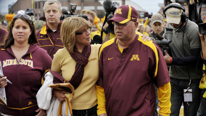 Minnesota coach Jerry Kill, front right, leaves the field with his wife, Rebecca, after Minnesota defeated Miami (Ohio) for Kill's first win at Minnesota in 2011. (AP)