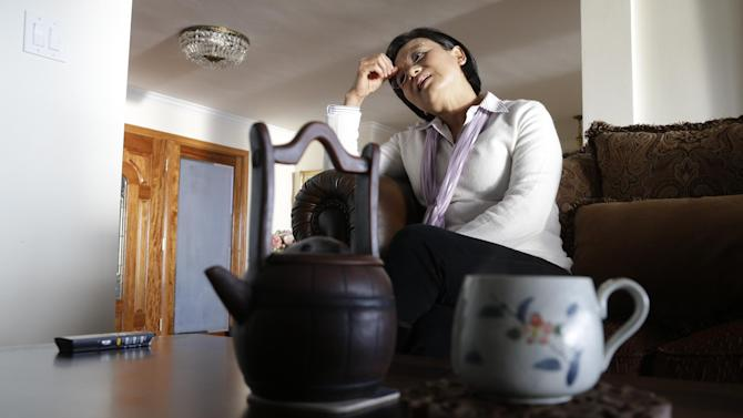 In this Monday, March 11, 2012 photo, Hong Li talks about her husband at their house in Rancho Palos Verdes, Calif. Hu Zhicheng had been arrested on charges of stealing Chinese state secrets. Even though authorities dropped all charges, he still isn't home because of a bizarre set of legal circumstances that prohibit him from leaving China. (AP Photo/Chris Carlson)