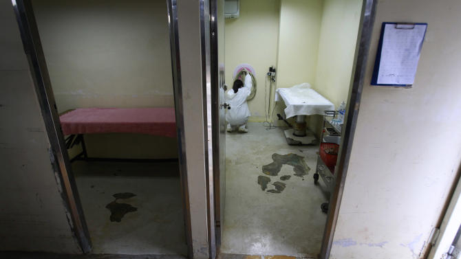 In this photo taken on Monday, April 9, 2012, a nurse prepares the room used to euthanize dogs at a government-run shelter in Taoyuan, northern Taiwan. In an ongoing project, Taiwanese photographer Tou Chih-kang makes portraits of shelter dogs in the final moments of their lives before being put down by lethal injection. Tou has been visiting shelters for two years now, capturing the images of some 400 canines, in hopes of educating the public on the proper care of pets. This year Taiwanese authorities will kill an estimated 80,000 stray dogs at 38 pounds scattered throughout the island. (AP Photo/Wally Santana)