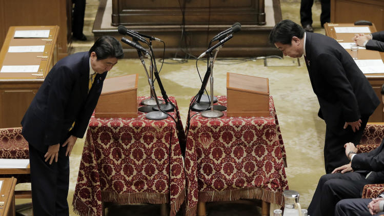 Japanese Prime Minister Yoshiko Noda, right, and Japan's main opposition Liberal Democratic Party President Shinzo Abe bow at each other before their debate at Parliament in Tokyo Wednesday, Nov. 14, 2012. During the heated parliamentary debate, Noda said that he is ready to dissolve the parliament by Friday, bringing an election within weeks, if Japan's main opposition party agrees to key electoral reforms. (AP Photo/Itsuo Inouye)