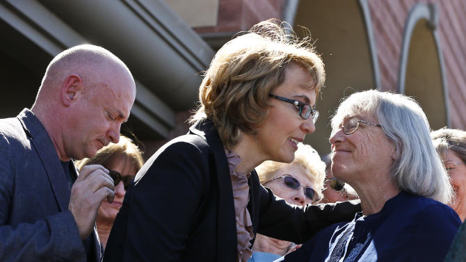 Former Rep. Gabrielle Giffords, middle, gets a kiss from Emily Nottingham, right, mother of slain former Giffords staffer Gabe Zimmerman, as they and Giffords husband Mark Kelly, left, and other surviving shooting victims and family members of the slain returned to the site of a shooting that left her critically wounded to urge key senators to support expanded background checks for gun purchases, Wednesday, March 6, 2013, in Tucson, Ariz. (AP Photo/Ross D. Franklin)