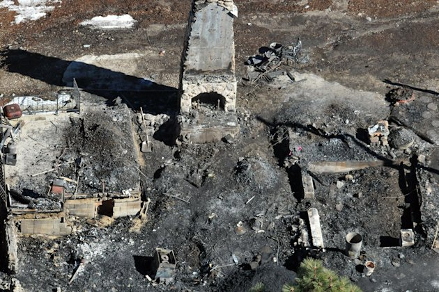 In this aerial photo, law enforcement authorities investigate the charred remnants of a cabin Wednesday, Feb. 13, 2013 in the Angeles Oaks area of Big Bear, Calif. An official briefed on the investiga