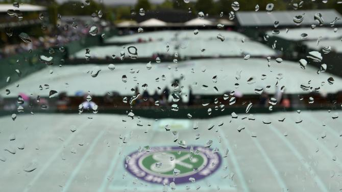 The Wimbledon logo is seen through raindrops on a window at the Wimbledon Tennis Championships in London