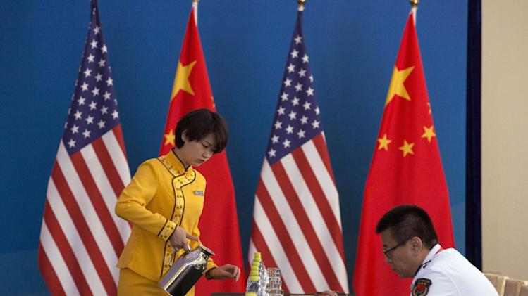 A hostess prepares drinks near a Chinese military officer before a Strategic Dialogue expanded meeting, part of the U.S.-China Strategic and Economic Dialogue (S&ED) in Beijing