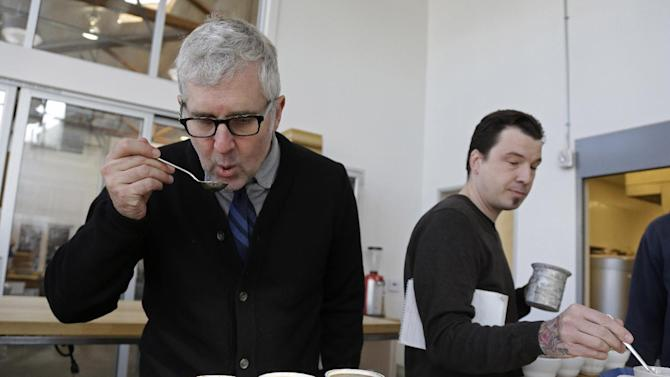 In this photo taken Thursday, Jan. 3, 2013, James Freeman, left, founder of Blue Bottle Coffee cups coffee samples, observing the tastes and aromas of brewed coffee from Uganda at his roastery in Oakland, Calif.  (AP Photo/Eric Risberg)
