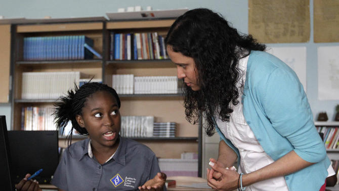 """In this May 1, 2012 photo, Mariatou Samou, left, a student in an Advanced Placement government class, speaks with her teacher, Kayla Morrow, during a lesson at the Academy for College and Career Exploration in Baltimore. In May 2012, 2 million students will take 3.7 million end-of-year AP exams - figures well over double those from a decade ago. """"What AP is really trying to teach you is for a lot of things, there's really not a right and wrong answer. It's, 'how do you get to that?'"""" Morrow said, adding the AP training improved her teaching in regular classes, too. (AP Photo/Patrick Semansky)"""