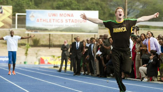 Britain's Prince Harry wins against Olympic sprint champion Usain Bolt, seen rear, by making a false start, Tuesday March 6 2012 at a mock race at the University of the West Indies, in Jamaica. Harry is touring the Caribbean as part of a Diamond Jubilee tour in honor of Queen Elizabeth II as she celebrates 60 years on the throne.  His visit comes as the new prime minister, Portia Simpson Miller, has called anew for the severing of ties with the British monarchy. (AP PhotoJohn Stillwell/PA) UNITED KINGDOM OUT  NO SALES  NO ARCHIVE