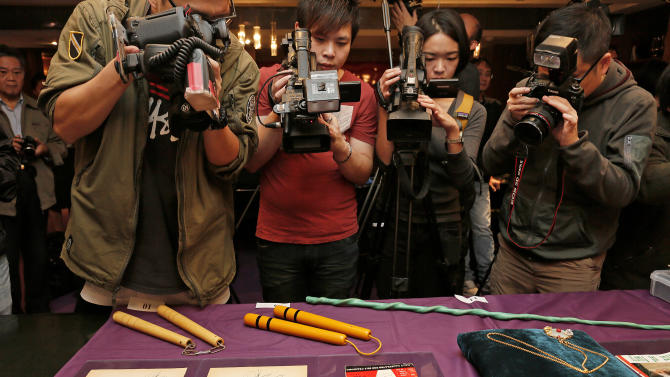 "Bruce Lee's most iconic martial arts weapons, including a pair of yellow lacquered wooden nunchaku, second from left, are displayed during an auction preview in Hong Kong, Monday, Dec. 2, 2013. It's part of a collection of 14 items including clothing and props going on the block on Thursday. Spink auction house estimates props from his movie ""Game of Death"" to be sold include the nunchaku expected to fetch $26,000-$38,700. (AP Photo/Vincent Yu)"