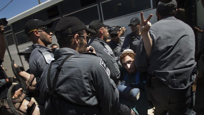 A Jewish settler flashes the victory sign while being evacuated by Israeli police forces from a house in the unauthorized West Bank Jewish settlement of Migron, Sunday, Sept. 2, 2012. Israel completed evacuation of Migron, culminating years of legal wrangling in a case that has become a rallying cry for hardline settler groups opposed to any withdrawal from occupied land claimed by the Palestinians. (AP Photo/Bernat Armangue)