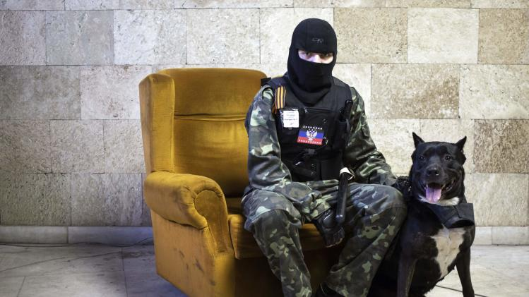 A masked pro-Russian protester poses inside a regional government building in Donetsk