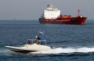 An Iranian Revolutionary Guard speedboat cruises past an oil tanker off the port of Bandar Abbas, southern Iran. The US Congress approved punishing new sanctions targeting Iran's energy and shipbuilding sectors, a day after President Barack Obama unveiled measures to cripple Tehran's nuclear drive