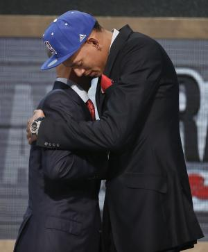 Baylor center Isaiah Austin, right, hugs NBA Commissioner Adam Silver after being granted ceremonial first round pick during the 2014 NBA draft, Thursday, June 26, 2014, in New York. Austin, who was projected to be a first round selection was diagnosed with Marfan syndrome just four days before the draft. (AP Photo/Jason DeCrow)