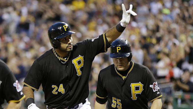 FILE - In this July 3, 2013 file photo, Pittsburgh Pirates' Pedro Alvarez (24) celebrates as he returns to the dugout with teammate Pirates' Russell Martin (55), who scored on his three-run home run off Philadelphia Phillies starting pitcher John Lannan during the fifth inning of a baseball game in Pittsburgh. Much of the focus as baseball heads into the second half is being placed on the possible suspensions of Alex Rodriguez, Ryan Braun and a handful of All-Stars implicated in the Biogenesis performance-enhancing drug scandal. Puigmania, a Pirates revival and one impressive power show in Baltimore should shift the gaze right back onto the field. (AP Photo/Gene J. Puskar, File)