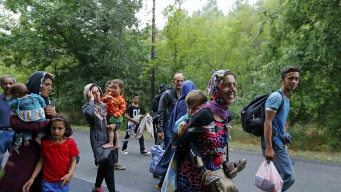 Afghan migrants walk down a road after crossing the border illegally from Serbia, near Asotthalom