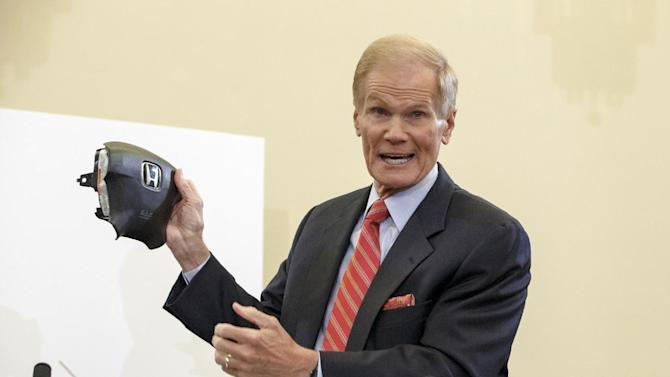 Senate Commerce Committee member Sen. Bill Nelson, D-Fla. displays the parts and function of a defective airbag made by Takata of Japan that has been linked to multiple deaths and injuries in cars driven in the US., Thursday, Nov. 20, 2014, during the committee's hearing on Capitol Hill in Washington. (AP Photo/J. Scott Applewhite)