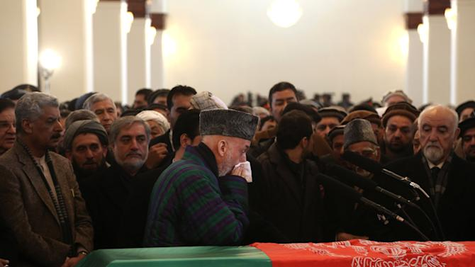 Afghan President Hamid Karzai, center, attends the funeral procession of Afghanistan's influential Vice President Mohammad Qasim Fahim in Kabul, Afghanistan, Tuesday, March 11, 2014. Fahim, a leading commander in the alliance that fought the Taliban who was later accused with other warlords of targeting civilian areas during the country's civil war, died on Sunday, March 9, 2014. He was 57. (AP Photo/Rahmat Gul)