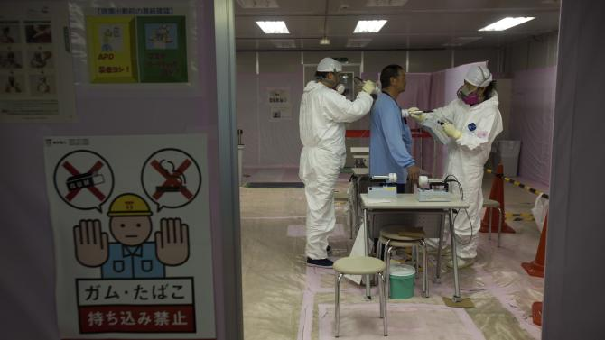 FILE - In this Nov. 12, 2011 file photo, a workers is given a radiation screening as he enters the emergency operation center at the crippled Fukushima Dai-ichi nuclear power station in Okuma, Japan, during a first media tour to Japan's tsunami-damaged nuclear power plant since the March 11 earthquake and tsunami. A growing number of Japanese workers who are risking their health to shut down the crippled Fukushima Dai-ichi nuclear power plant are suffering from depression, anxiety about the future and a loss of motivation, say two doctors who visit them regularly. (AP Photo/David Guttenfelder, Pool, File)