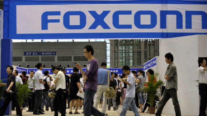 FILE - In this file photo taken on May 22, 2010, visitors to a job fair walk past the Foxconn recruitment area in Shenzhen in south China's Guangdong province. The New York-based China Labor Watch has reported that 3,000 to 4,000 workers at the factory in Zhengzhou city went on strike Friday Oct. 5, 2012 over increased quality control demands and having to work during an extended national holiday. Foxconn Technology Group said Saturday that production at its central Chinese factory that makes Apple's iPhones was continuing without interruption, denying a labor watch group's report that thousands of workers at the plant had gone on strike. (AP Photo, File) CHINA OUT