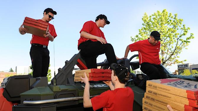 IMAGE DISTRIBUTED FOR PIZZA HUT - Pizza Hut delivery drivers unload pizzas during a unique delivery from aboard the Halo Warthog during an event promoting the launch of the Pizza Hut for Xbox Live ordering app on Tuesday, April 23, 2013 at the Microsoft in Seattle, WA. (Rod Mar/AP Images for Pizza Hut)