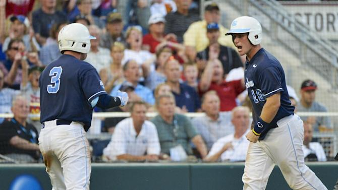 North Carolina's Brian Holberton, right, celebrates with teammate Mike Zolk (3) after scoring against North Carolina State in the fourth inning of an NCAA College World Series elimination baseball game in Omaha, Neb., Thursday, June 20, 2013. (AP Photo/Ted Kirk)