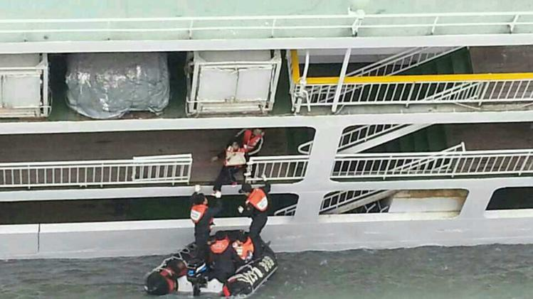 A passenger is rescued by South Korean maritime policemen from a sinking ship in the sea off Jindo