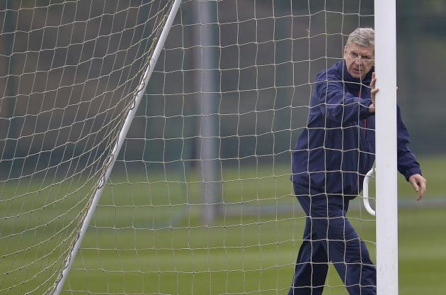 Arsenal manager Arsene Wenger moves a goalpost during a training session at London Colney near London