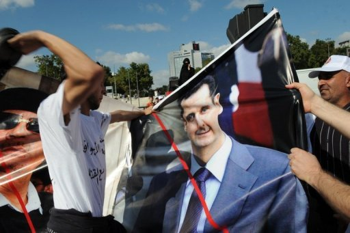 A Syrian opponent hits a picture of Syrian president Bashar al-Assad (R)