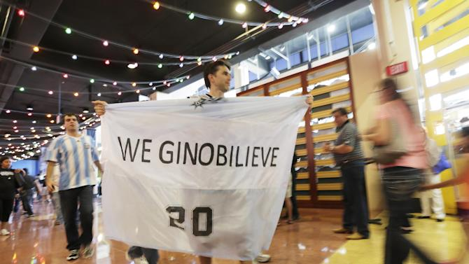 A San Antonio Spurs fan arrives carrying a banner for Manu Ginobili before Game 5 of the NBA Finals basketball series against the Miami Heat, Sunday, June 16, 2013, in San Antonio. (AP Photo/Eric Gay)