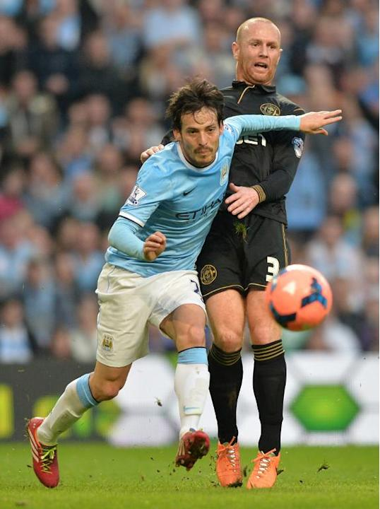 Manchester City's David Silva (L) and Wigan Athletic's Stephen Crainey during their FA Cup match at the Etihad Stadium on March 9, 2014