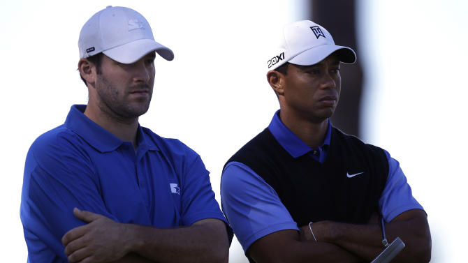 Tiger Woods, right, stands with his amateur partner, Dallas Cowboys NFL football quarterback Tony Romo, at the 18th hole at Spyglass Hill Golf Course during the first round of the Pebble Beach National Pro-Am golf tournament in Pebble Beach, Calif., Thursday, Feb. 9, 2012. (AP Photo/Marcio Jose Sanchez)
