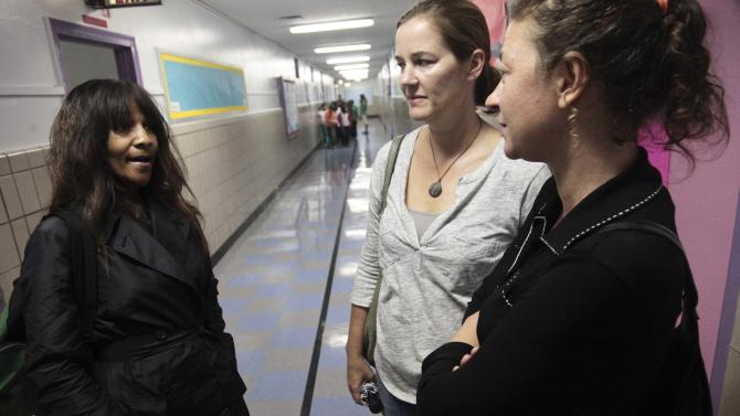 April Gayles, left, Jen Zunt, center, Lea Mansour, chat as they leave the PTA office at  P.S. 75 on Friday, Sept. 28, 2012 in New York.  Neighborhood residents are in turmoil over an adult shelter near the school on 95th Street, saying they were blindsided by the suddenness of the shelter's opening. Zunt, a mother of a fifth grader at the school, said she is concerned about safety and the mental state of residents at the shelter.  (AP Photo/Bebeto Matthews)