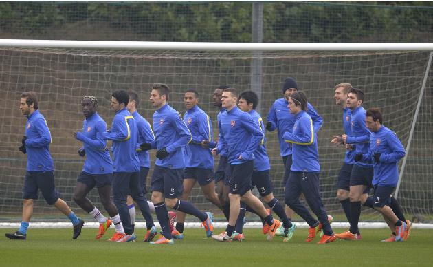 Arsenal team members warm up during a training session at London Colney near London