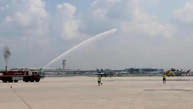 A fire truck gives a water salute for an CF-188 Hornet during media day for the Canadian International Air Show at Pearson Airport in Toronto,